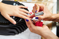 Nails painting with UV dry lamp in blue light Stock Images