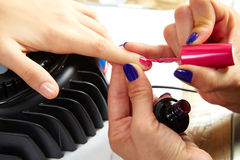 Nails painting with UV dry lamp in blue light Royalty Free Stock Images