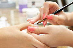 Nails painting woman with brush in Nail Salon Royalty Free Stock Images