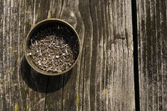 Nails in rusty tin can on a wooden background. Nails in a rusty tin can on a wooden background Royalty Free Stock Photo