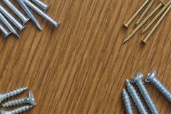 Nails and screws on a wooden background with copy space. Macro shoot Stock Photo