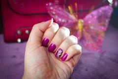 Nails täckte med stelnar färg och dekorerat med en guld- butterf Royaltyfria Bilder