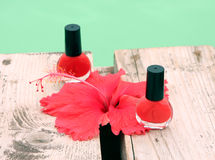 Nails varnish. Red nails varnish and flower along a pool Stock Photography