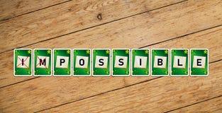 Naipes con el texto 'imposible 'en un piso de madera foto de archivo libre de regalías