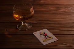 Naipes y copa de vino del coñac en la tabla de madera Foto de archivo