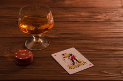Naipes y copa de vino del coñac en la tabla de madera Fotografía de archivo