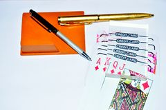 Naipes y pluma de la tarjeta de cr?dito en el fondo blanco para jugar imagen de archivo libre de regalías