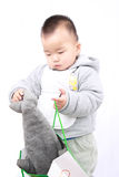 Naive baby. A naive child's clumsy behavior,the chinese baby put a toy dolphin into a bag Stock Photos
