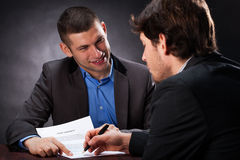 Naive man signing the usury contract. With crook Royalty Free Stock Images