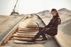 Najeźdźcy dziewczyna w rzemiennym kostiumu z crossbow przy apokaliptycznym światem Fotografia Royalty Free