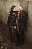 Najeźdźcy kobieta w rzemiennym kostiumu z łękiem przy apokaliptycznym światem i mężczyzna Zdjęcia Royalty Free