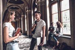 najlepsi przyjaciele Młodzi uśmiechnięci ucznie stoi w uniwersyteckiej sala i mówją z each inny zdjęcia stock