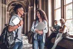 najlepsi przyjaciele Młodzi uśmiechnięci ucznie stoi w uniwersyteckiej sala i mówją z each inny obraz royalty free
