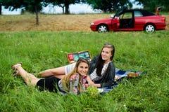 Najlepsi przyjaciele ma pinkin obok ich samochodu zdjęcia royalty free