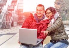 Najlepsi przyjaciele patrzeje zaskakujący z komputerowym laptopem Zdjęcie Stock