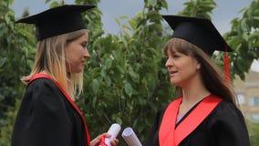 Najlepszy żeńscy przyjaciele trzyma dyplomy i gawędzi w parku w akademickich sukniach zbiory