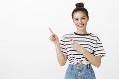 Najlepszy reklama kiedykolwiek Zadowolona ufna kobieta w pasiastej koszulce, wskazuje przy górnym lewym kątem z palcami wskazując obraz stock