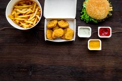 Najwięcej popularnego fasta food posiłku Chiken bryłki, hamburgery i francuscy dłoniaki na ciemnej drewnianej tło odgórnego widok fotografia stock