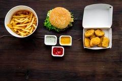 Najwięcej popularnego fasta food posiłku Chiken bryłki, hamburgery i francuscy dłoniaki na ciemnej drewnianej tło odgórnego widok obraz stock