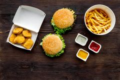 Najwięcej popularnego fasta food posiłku Chiken bryłki, hamburgery i francuscy dłoniaki na ciemnej drewnianej tło odgórnego widok zdjęcia stock