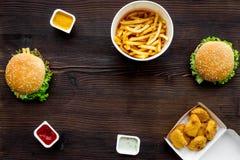 Najwięcej popularnego fasta food posiłku Chiken bryłki, hamburgery i francuscy dłoniaki na ciemnej drewnianej tło odgórnego widok zdjęcie royalty free