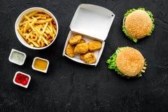 Najwięcej popularnego fasta food posiłku Chiken bryłki, hamburgery i francuscy dłoniaki na czarnej tło odgórnego widoku kopii prz zdjęcia royalty free