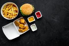 Najwięcej popularnego fasta food posiłku Chiken bryłki, hamburgery i francuscy dłoniaki na czarnej tło odgórnego widoku kopii prz obrazy stock