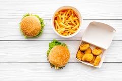 Najwięcej popularnego fasta food posiłku Chiken bryłki, hamburgery i francuzów dłoniaki na białego drewnianego tła odgórnym widok obraz stock