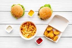 Najwięcej popularnego fasta food posiłku Chiken bryłki, hamburgery i francuzów dłoniaki na białego drewnianego tła odgórnym widok obraz royalty free