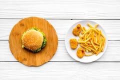 Najwięcej popularnego fasta food posiłku Chiken bryłki, hamburgery i francuzów dłoniaki na białego drewnianego tła odgórnym widok zdjęcia royalty free