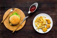 Najwięcej popularnego fasta food posiłku Chiken bryłki, hamburgery i francuzów dłoniaki na ciemnego drewnianego tła odgórnym wido obraz stock