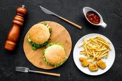Najwięcej popularnego fasta food posiłku Chiken bryłki, hamburgery i francuzów dłoniaki na czarnego tła odgórnym widoku, fotografia stock