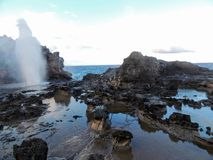 Nakalele blåshål med vatten som ut besprutar som skapades från Stilla havetvågor som slår den högväxta steniga klippakustlinjen,  Arkivbilder