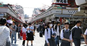 Nakamise-dori in Asakusa. Tokyo, Japan - April 19, 2017: crowd of people in spring sakura on Nakamise-dori, street with food and souvenirs shops, connetting the Royalty Free Stock Photo