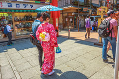 Nakamise-dori in Asakusa. Tokyo, Japan - April 19, 2017: woman wearing kimono with parasol, the national tradition costume of Japan, walking on Nakamise-dori, a Stock Photos