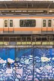 Nakano Station wall decorated with children drawing of sea related fishes and shells surrounding by a JR Chuo Line train.  stock photography