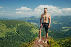 Naked athletic man standing on the mountain rock Royalty Free Stock Photos