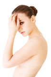Naked attractive woman touching her forehead. Royalty Free Stock Photos