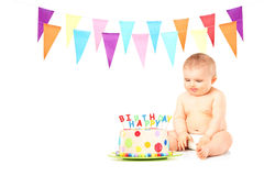 Naked baby boy looking at a delicious birthday cake. Isolated on white background Stock Photo