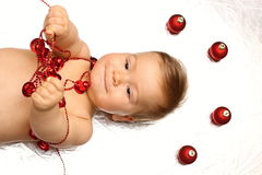 Naked baby boy playing with red christmas decorations. Naked baby boy playing with red christmas bells with decorations above Stock Photo