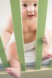 Naked baby in a diaper sitting in a crib. And holding on safety fence stock image
