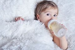 Naked baby drinks from bottle. Naked baby drinks from a bottle while lying on the bed Stock Photos