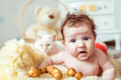 Naked baby lying on blanket. Naked baby lying on a yellow soft blanket with decorated golden nuts in the room Stock Photos