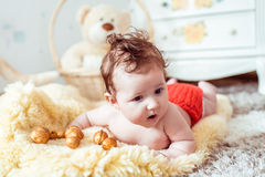 Naked baby lying on blanket. Naked baby lying on a yellow soft blanket with decorated golden nuts in the room Royalty Free Stock Photography