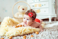 Naked baby lying on blanket. Naked baby lying on a yellow soft blanket with decorated golden nuts in the room Royalty Free Stock Photo
