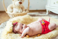 Naked baby lying on blanket. Naked baby lying on a yellow soft blanket with decorated golden nuts in the room Stock Images