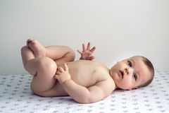 Naked baby lying on his back. On the diaper royalty free stock photos