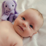 Naked baby with a toy. Close-up portrait of naked baby with a toy rabbit Royalty Free Stock Photo