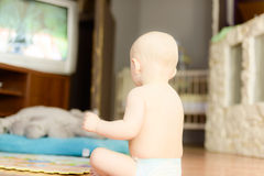 Naked baby watching TV sitting on the floor Royalty Free Stock Image