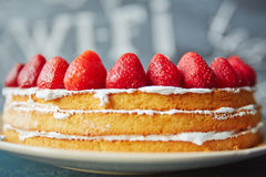 Naked Biscuit Cake in Cafe. Closeup shot of simple biscuit naked cake decorated with fresh ripe strawberries on top and white icing between layers royalty free stock photography